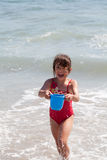 Little Girl Playing with a Bucket on the Beach Stock Photography