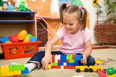 Little girl is playing with building bricks Stock Photos