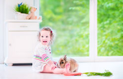 Little girl playing with a bunny Stock Photography