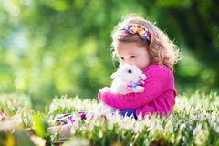 Little girl playing with bunny on Easter egg hunt Royalty Free Stock Photos