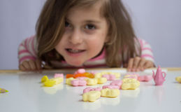 Little girl playing with candies Royalty Free Stock Image