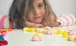 Little girl playing with candies Royalty Free Stock Photo