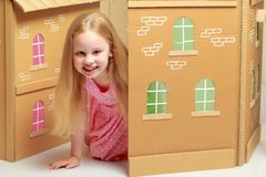 A little girl is playing in a cardboard house Royalty Free Stock Photos