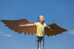 Little girl playing with cardboard toy wings in the park at the Stock Photo