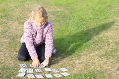 Little girl playing cards Stock Photos