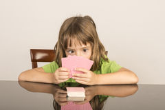 Little girl playing cards Stock Photography