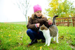 Little girl playing with cat Stock Images