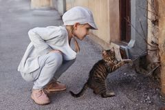 Little girl playing with a cat Royalty Free Stock Image
