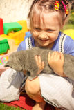 little girl playing with a cat outdoors Royalty Free Stock Images