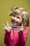 Little girl playing cats cradle game Stock Image