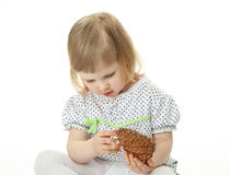 Little girl playing with cedar cone Stock Images