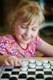 Little girl playing checkers stock images