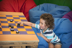 Little girl is playing checkers. Stock Photography
