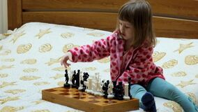 Little girl is playing chess stock video