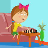 Little girl playing chess sitting on sofa in room. Little girl playing chess sitting on a sofa in room Stock Image