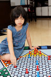 Little girl playing Chinese checker game. A little chinese girl learning to play Chinese checker game stock image