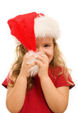 Little girl playing with christmas hat Royalty Free Stock Photos