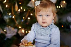 Little girl is playing with Christmas presents at the Christmas tree stock photo