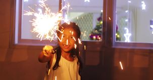Little girl playing Christmas sparklers at home stock footage