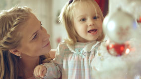 Little girl playing with Christmas toy near the Christmas tree with mother Royalty Free Stock Photos