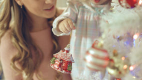 Little girl playing with Christmas toy near the Christmas tree with mother Stock Photo