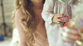 Little girl playing with Christmas toy near the Christmas tree with mother Stock Image
