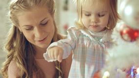 Little girl playing with Christmas toy near the Christmas tree with mother Stock Images