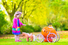 Little girl playing Cinderella. Cute curly little girl playing Cinderella fairy tale holding a magic wand next to a pumpkin carriage having fun in an autumn park Royalty Free Stock Photo
