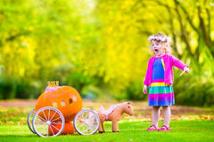 Little girl playing Cinderella. Cute curly little girl playing Cinderella fairy tale holding a magic wand next to a pumpkin carriage having fun in an autumn park Royalty Free Stock Images