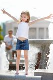 Little girl playing with a city fountain Royalty Free Stock Image