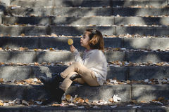 Little girl playing in a city park in autumn Stock Photo