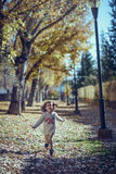 Little girl playing in a city park in autumn Stock Photos