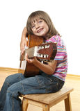 Little girl playing classical guitar Stock Photos