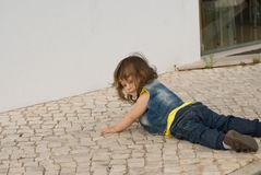 The little girl  is playing on the cobblestone Royalty Free Stock Image