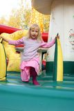 Little girl playing in color bouncy castle. Outdoor Royalty Free Stock Photo