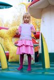 Little girl playing in color bouncy castle. Outdoor Royalty Free Stock Photos