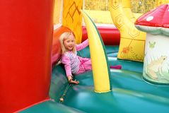 Little girl playing in color bouncy castle. Outdoor Stock Image