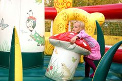 Little girl playing in color bouncy castle. Outdoor Royalty Free Stock Images
