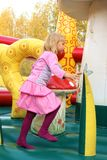 Little girl playing in color bouncy castle. Outdoor Royalty Free Stock Photography