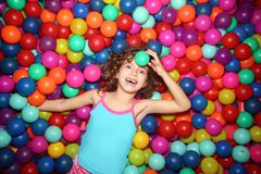 Little girl playing in colorful balls playground Royalty Free Stock Photos