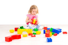 Little girl playing with colorful blocks stock photos