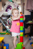 Little girl playing with colorful plastic blocks Stock Photos