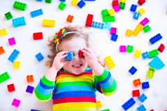 Little girl playing with colorful toy blocks Stock Images