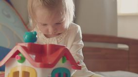 Little girl playing with colorful toys on the bed of the parents . stock footage