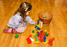 Little girl playing with colorful wooden blocks. Little girl playing happily with colorful wooden blocks sitting on the floor Royalty Free Stock Images