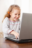 Little girl playing computer Stock Images