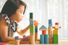 Little girl playing with construction toy blocks building a tower royalty free stock image