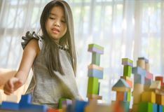 Little girl playing with construction toy blocks building a tower royalty free stock images