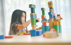 Little girl playing with construction toy blocks building a tower stock image