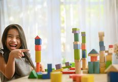 Little girl playing with construction toy blocks building a tower stock photo